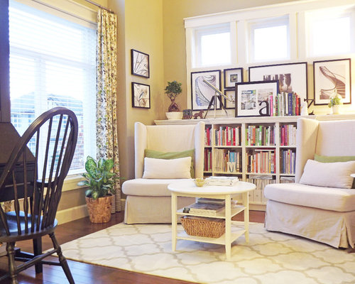 Shabby-chic style living room library idea in Vancouver with beige walls