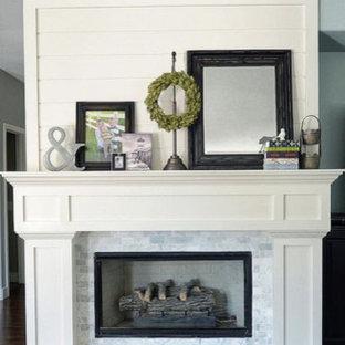 Imagen de salón para visitas cerrado, clásico, de tamaño medio, sin televisor, con paredes grises, suelo de madera oscura, chimenea tradicional, marco de chimenea de piedra y suelo marrón