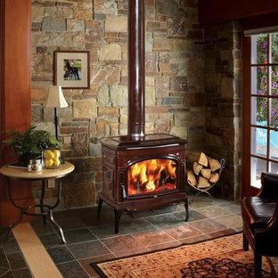 Foto de salón cerrado, rústico, de tamaño medio, con suelo de pizarra, estufa de leña, marco de chimenea de metal y suelo gris