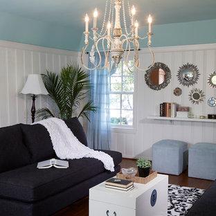 Esempio di un soggiorno costiero di medie dimensioni e chiuso con angolo bar, pareti blu, pavimento in legno massello medio, camino sospeso, cornice del camino in cemento e TV nascosta