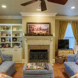 Esempio di un soggiorno american style di medie dimensioni e aperto con pareti beige, pavimento in legno massello medio, camino classico, cornice del camino piastrellata, nessuna TV e pavimento marrone