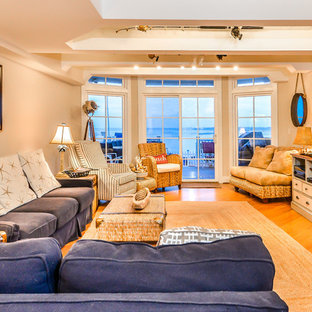 Inspiration for a large beach style enclosed medium tone wood floor living room remodel in DC Metro with white walls, a corner fireplace, a stone fireplace and a wall-mounted tv