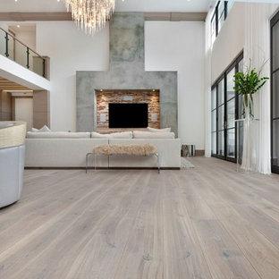 Inredning av ett modernt mycket stort allrum med öppen planlösning, med vita väggar, ljust trägolv och en väggmonterad TV