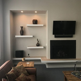 Example of a mid-sized trendy enclosed carpeted and gray floor living room design in Phoenix with beige walls, a standard fireplace, a plaster fireplace and a wall-mounted tv