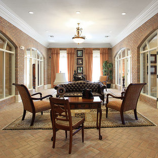 Inspiration for a large traditional formal enclosed living room in New Orleans with brown walls, brick floors, no fireplace, no tv and brown floor.