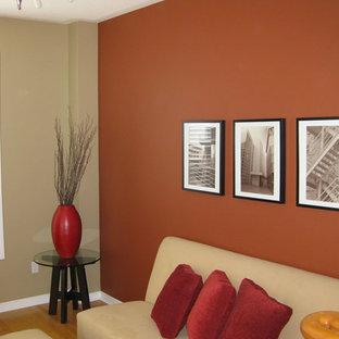 Ejemplo de salón cerrado, actual, de tamaño medio, con parades naranjas y suelo de madera en tonos medios
