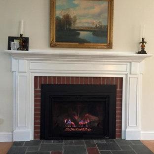 Foto de salón para visitas tradicional, de tamaño medio, sin televisor, con paredes amarillas, suelo de madera en tonos medios, chimenea tradicional, marco de chimenea de ladrillo y suelo marrón