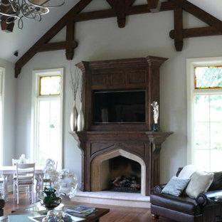 Esempio di un soggiorno stile rurale di medie dimensioni e aperto con parete attrezzata, pareti grigie, parquet scuro, camino classico, cornice del camino in pietra e pavimento marrone