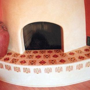 Mittelgroßes Mediterranes Wohnzimmer mit roter Wandfarbe, Eckkamin, verputztem Kaminsims und braunem Boden in Santa Barbara