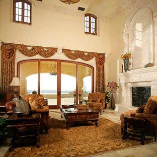 サンディエゴの大きい地中海スタイルのおしゃれな独立型リビング (フォーマル、ベージュの壁、トラバーチンの床、標準型暖炉、石材の暖炉まわり、テレビなし) の写真