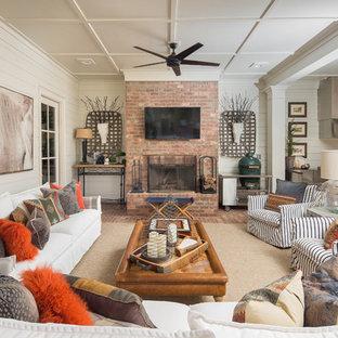 На фото: гостиные комнаты в классическом стиле с кирпичным полом, стандартным камином, фасадом камина из кирпича и телевизором на стене