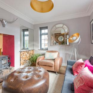 Modelo de salón cerrado, contemporáneo, pequeño, con paredes púrpuras, suelo de madera clara, suelo beige y estufa de leña