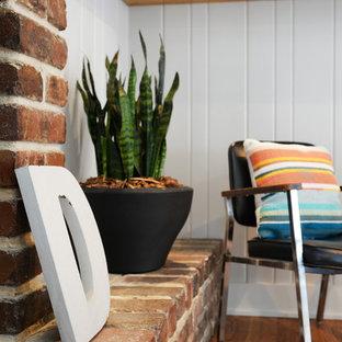 カンザスシティの中サイズのトラディショナルスタイルのおしゃれなLDK (マルチカラーの壁、カーペット敷き、標準型暖炉、レンガの暖炉まわり、壁掛け型テレビ、グレーの床) の写真