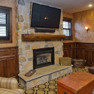 タンパの中くらいのトラディショナルスタイルのおしゃれな独立型リビング (茶色い壁、カーペット敷き、吊り下げ式暖炉、石材の暖炉まわり、壁掛け型テレビ、マルチカラーの床) の写真