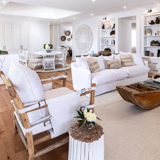 Large beach style open concept living room in Other with white walls, medium hardwood floors, a built-in media wall and brown floor.