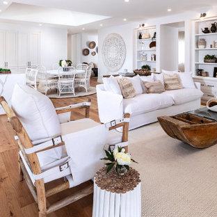 Modelo de salón abierto, costero, grande, con paredes blancas, suelo de madera en tonos medios, pared multimedia y suelo marrón