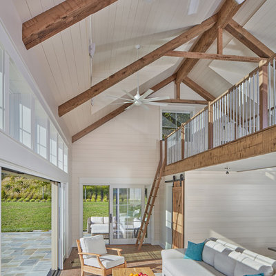 Inspiration for a country loft-style brown floor and medium tone wood floor living room remodel in DC Metro with beige walls