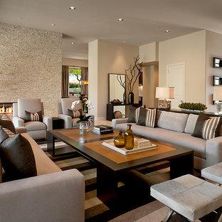 На фото: гостиная комната в современном стиле с фасадом камина из камня с