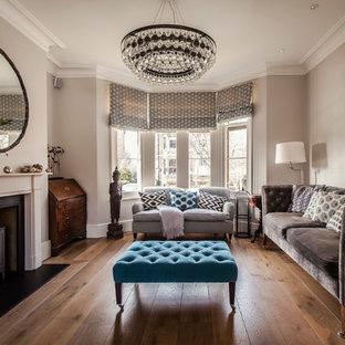 Ejemplo de salón para visitas tradicional renovado, de tamaño medio, sin televisor, con paredes grises, suelo de madera en tonos medios y estufa de leña