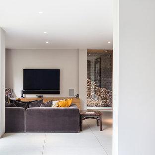 Ispirazione per un grande soggiorno vittoriano chiuso con sala formale, pareti grigie, pavimento in laminato, camino classico, cornice del camino in pietra, TV a parete e pavimento marrone