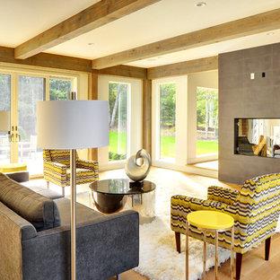 Idee per un grande soggiorno minimal aperto con pareti grigie, parquet chiaro, camino bifacciale e cornice del camino in cemento