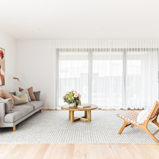 Inspiration for a scandinavian living room in Melbourne with white walls, light hardwood floors and beige floor.