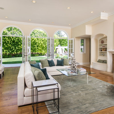 Living room - large transitional formal and enclosed dark wood floor and brown floor living room idea in Los Angeles with beige walls, a standard fireplace, a stone fireplace and no tv