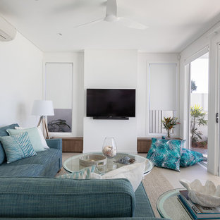 Photo of a mid-sized beach style living room in Other with white walls, a wall-mounted tv and beige floor.