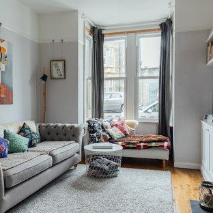 Diseño de salón cerrado, escandinavo, con paredes grises, suelo de madera en tonos medios, estufa de leña, marco de chimenea de metal, televisor independiente y suelo marrón
