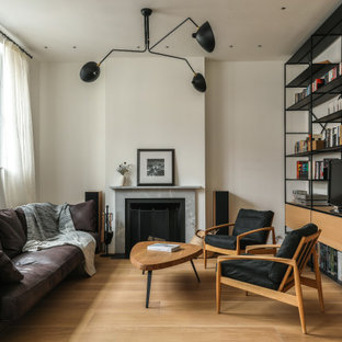 This is an example of a medium sized contemporary formal enclosed living room in London with white walls, medium hardwood flooring, a standard fireplace, a tiled fireplace surround, no tv and beige floors.
