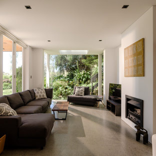 This is an example of a beach style living room in Sydney with white walls, concrete floors, a standard fireplace and grey floor.