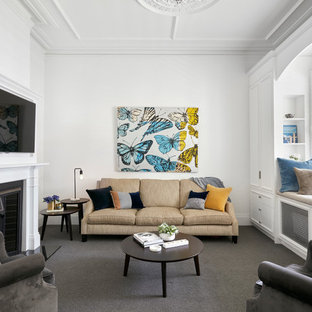 Design ideas for a transitional living room in Melbourne with white walls, carpet, a standard fireplace, a wall-mounted tv and grey floor.