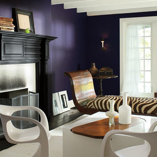 Idee per un grande soggiorno minimal aperto con pareti viola, parquet scuro, camino classico, cornice del camino in metallo, nessuna TV e pavimento marrone