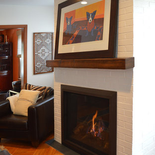 Example of an eclectic living room design in New York with white walls, a standard fireplace and a brick fireplace