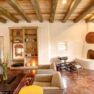 アルバカーキのサンタフェスタイルのおしゃれなリビング (コーナー設置型暖炉、漆喰の暖炉まわり) の写真