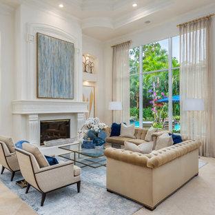 Modelo de salón abierto y casetón, mediterráneo, grande, sin televisor, con paredes blancas, suelo de mármol, chimenea tradicional, marco de chimenea de yeso y suelo beige