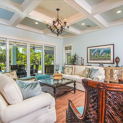 Inspiration for a tropical formal and open concept porcelain tile living room remodel in Miami with blue walls