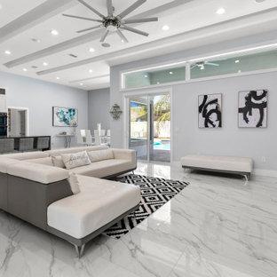 Esempio di un soggiorno costiero con pareti grigie, pavimento in marmo, camino classico, cornice del camino piastrellata, parete attrezzata, pavimento grigio e soffitto ribassato