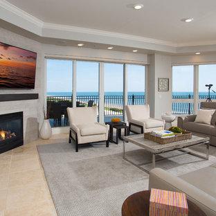 オーランドの大きいビーチスタイルのおしゃれなLDK (フォーマル、ベージュの壁、トラバーチンの床、標準型暖炉、石材の暖炉まわり、壁掛け型テレビ、ベージュの床) の写真