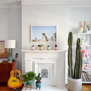 Immagine di un grande soggiorno bohémian chiuso con angolo bar, pareti blu, camino classico, nessuna TV, pavimento marrone e pavimento in legno massello medio