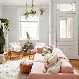 ニューヨークのエクレクティックスタイルのおしゃれなリビング (淡色無垢フローリング、標準型暖炉、テレビなし、マルチカラーの壁) の写真
