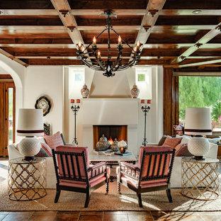 Mediterranes Wohnzimmer mit weißer Wandfarbe, Kamin und braunem Boden in Los Angeles