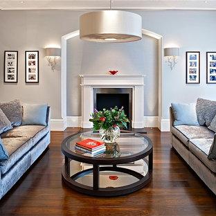 Modelo de salón tradicional renovado con paredes grises, chimenea tradicional y suelo marrón
