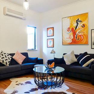 Inspiration for a contemporary formal medium tone wood floor living room remodel in Perth with white walls