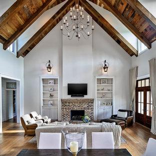 Imagen de salón abierto, campestre, grande, con paredes grises, suelo de madera clara, chimenea tradicional, marco de chimenea de ladrillo, televisor colgado en la pared y suelo marrón