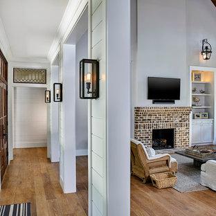 アトランタの広いカントリー風おしゃれなLDK (グレーの壁、淡色無垢フローリング、標準型暖炉、レンガの暖炉まわり、壁掛け型テレビ、茶色い床) の写真