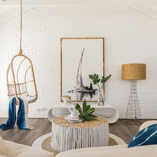 Beach style living room in Perth with white walls, medium hardwood floors and brown floor.
