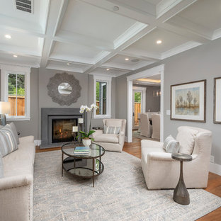 This is an example of a classic formal enclosed living room in San Francisco with grey walls, a standard fireplace, a concrete fireplace surround and medium hardwood flooring.