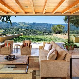 Réalisation d'un très grand salon sud-ouest américain ouvert avec un mur jaune, une salle de réception, un sol en bois clair, aucune cheminée, aucun téléviseur et un sol beige.