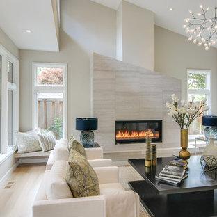 Idée de décoration pour un grand salon design fermé avec un mur beige, un sol en bois clair, un manteau de cheminée en carrelage, une salle de réception, une cheminée ribbon, aucun téléviseur et un sol beige.